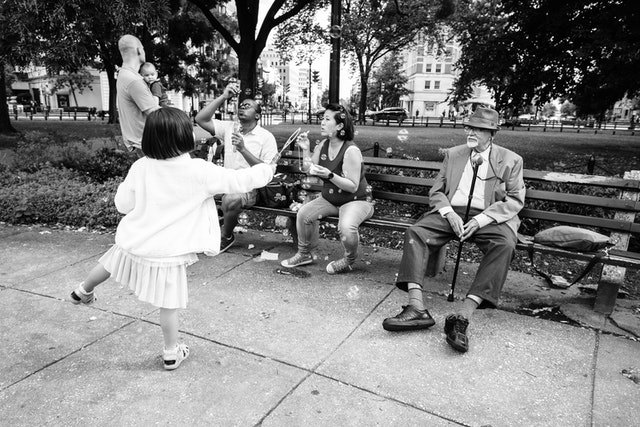 People blowing soap bubbles sitting on the benches of Dupont Circle.