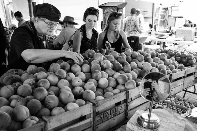 Three women shopping for peaches at Eastern Market in Washington, DC.