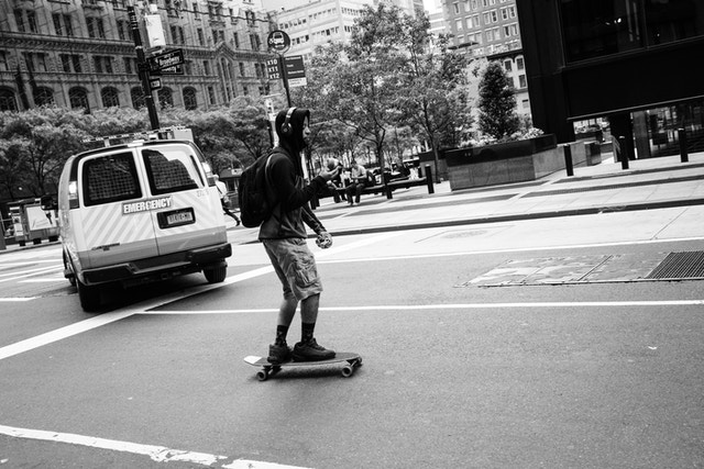 A man riding a skateboard while eating an apple, on Broadway, in the Financial District.