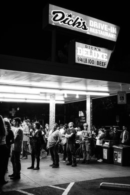 A line of people waiting to order food at night at Dick's Drive-In Restaurant in Capitol Hill, Seattle.