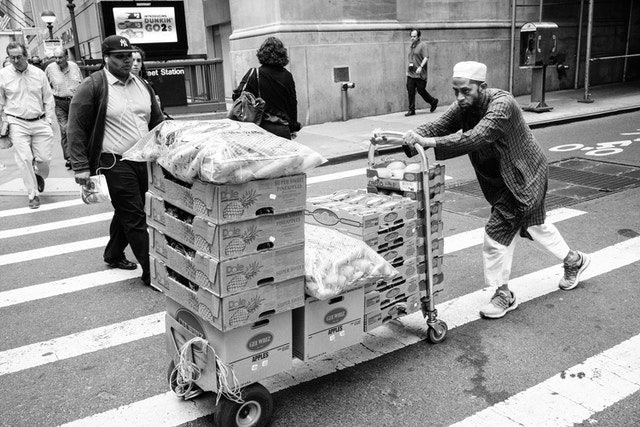 A man pushing a cart full of fruits and vegetables on William Street in New York's Financial District.