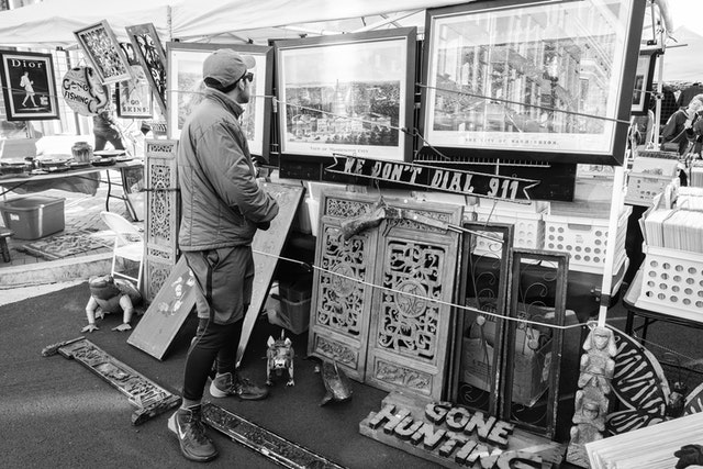A person looking at artwork at the Eastern Market Flea Market in Washington, DC.