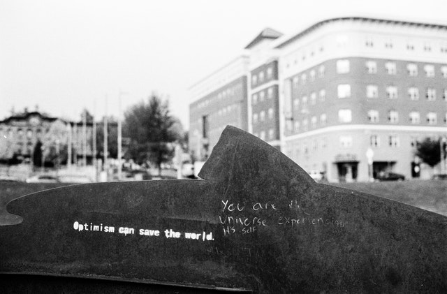 """Graffiti on a sculpture in Winooski, Vermont: """"Optimism can save the world"""" and """"you are the universe experiencing its self [sic]"""""""