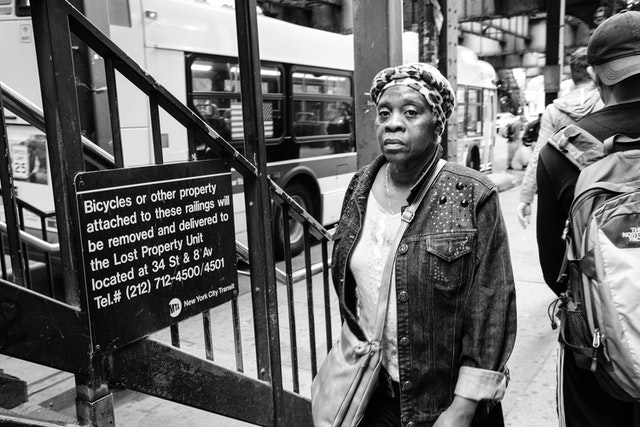 A woman in a denim jacket walking on Broadway, next to the stairs leading up to the Marcy Avenue subway station in Williamsburg.