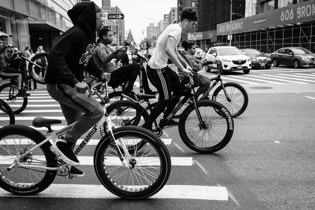 A group of teenagers on bicycles on Broadway & Houston Street, near Soho, Manhattan.