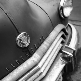 A close-up of the hood ornament on a rusted 1940s Oldsmobile.
