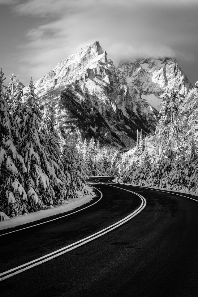 A winding road flanked by snow-covered trees. In the background, Teewinot Mountain, with Grand Teton and Mount Owen obscured by clouds.