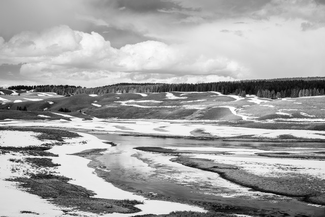 The Yellowstone River in Yellowstone National Park. Its banks are covered on snow, and in the background, rolling hills and a line of trees can be seen.