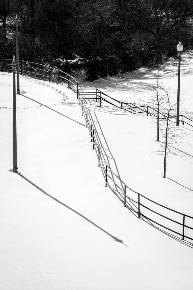 A curved fence in a snow-covered Anacostia Park.