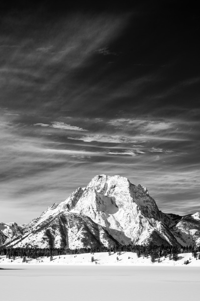 Mount Moran and a snow-covered frozen Jackson Lake, and lots of wispy clouds in the sky.