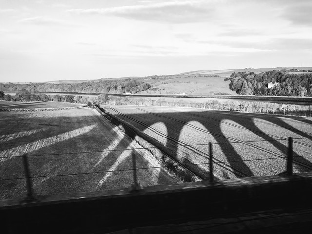 The shadows of the arched railway on the fields of Berwich-upon-Tweed, England, seen from the train.