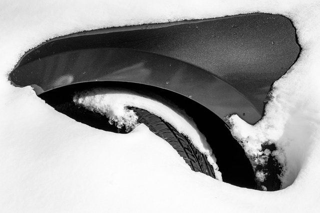 The wheel well of a car completely buried in snow.