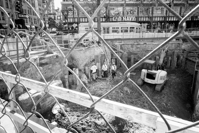 A group of construction workers seen through a chainlink fence on Stockton & Market, San Francisco.
