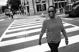 A woman in a striped shirt walking on a crosswalk on 14th & U in Washington, DC.