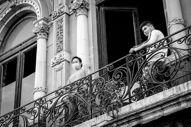 Two construction workers on a balcony in Mexico City.