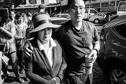 A young man walking with his arm around an older lady wearing a hat on Pike Place Market.