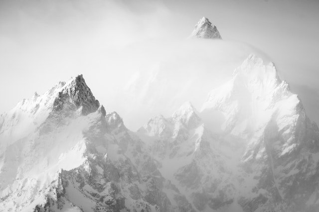 A close-up of the Cathedral Range of the Tetons, seen partially shrouded in clouds in morning light from the Willow Flats Turnout.