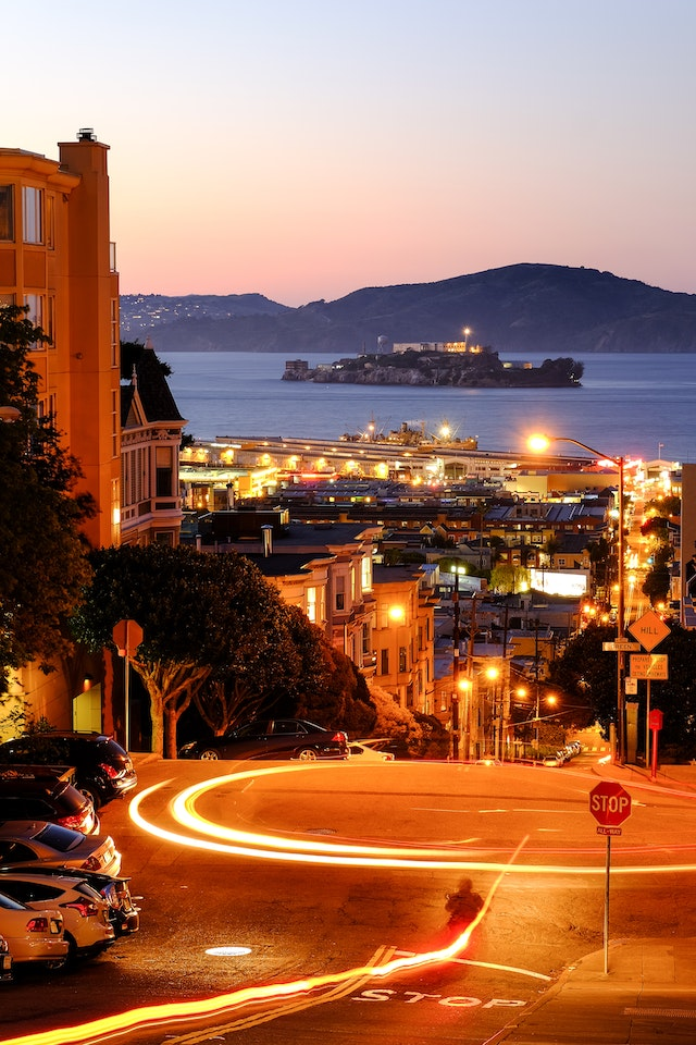 Taylor Street in San Francisco, at dusk, with Alcatraz Island in the distance.