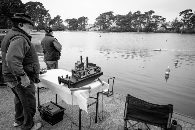 A group of men driving R/C boats at Spreckels Lake in Golden Gate Park, San Francisco.