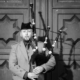 A man playing the bagpipes on the Royal Mile of Edinburgh.
