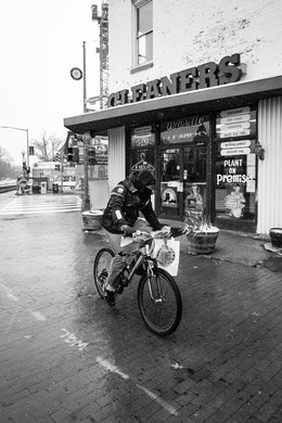 A man carrying a bag of Popeyes bikes past a dry cleaning business on Capitol Hill.