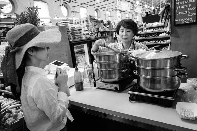 A customer shopping for dumplings at Eastern Market, while the salesperson pulls them out of the steamer and into the container.