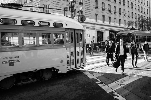Pedestrians crossing the street in front of an old streetcar on Market Street.