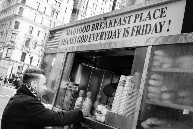 "A man buying breakfast from a cart with a sign that says ""thanks god everyday is friday!"" [sic]"