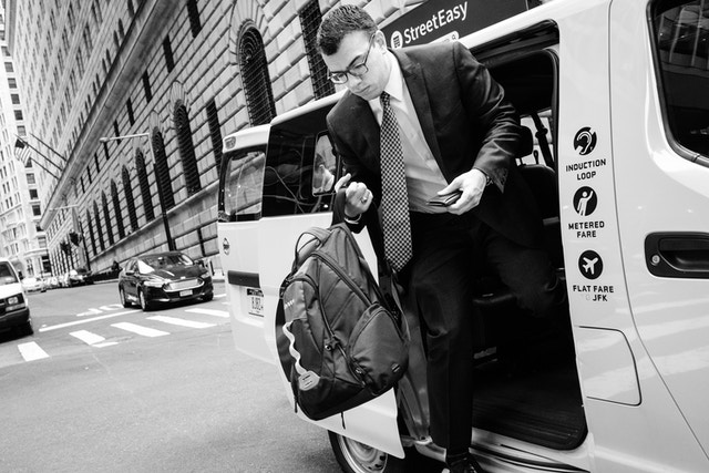 A man in a suit exiting a cab on William Street in New York City.