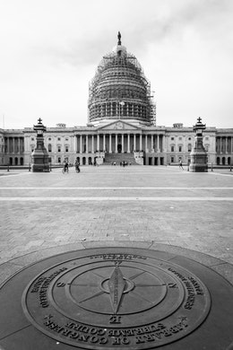 The compass on the grounds of the United States Capitol, with the scaffolding-covered dome in the background.