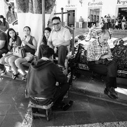 A man getting his shoes polished at the main square in Taxco.