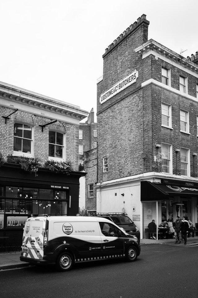 A Thames Water van parked on the street in front of a building with a Lidstone & Co. Butchers sign.