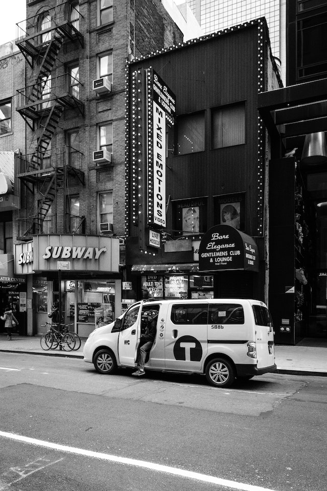 A man getting out of a taxi in front of an adult store in New York City.