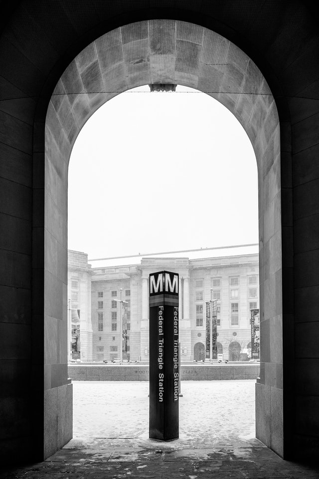 The arched exit of the Federal Triangle Metro Station at the Ronald Reagan Building, with the Metro sign under it.