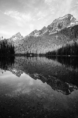The Tetons reflected off the still waters of String Lake, at Grand Teton National Park. Grand Teton can be seen in the background.