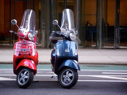 Two Vespa scooters parked on the street.