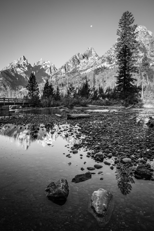 Rocks in the String Lake outlet. In the background, Teewinot Mountain, Grand Teton, Mount Owen, and Symmetry Spire.