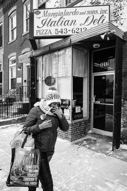 A woman protecting her face from the cold with her scarf, as she walks in front of a sandwich shop on Capitol Hill.
