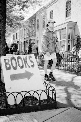 "A person walking in front of a ""books"" sign in Eastern Market."