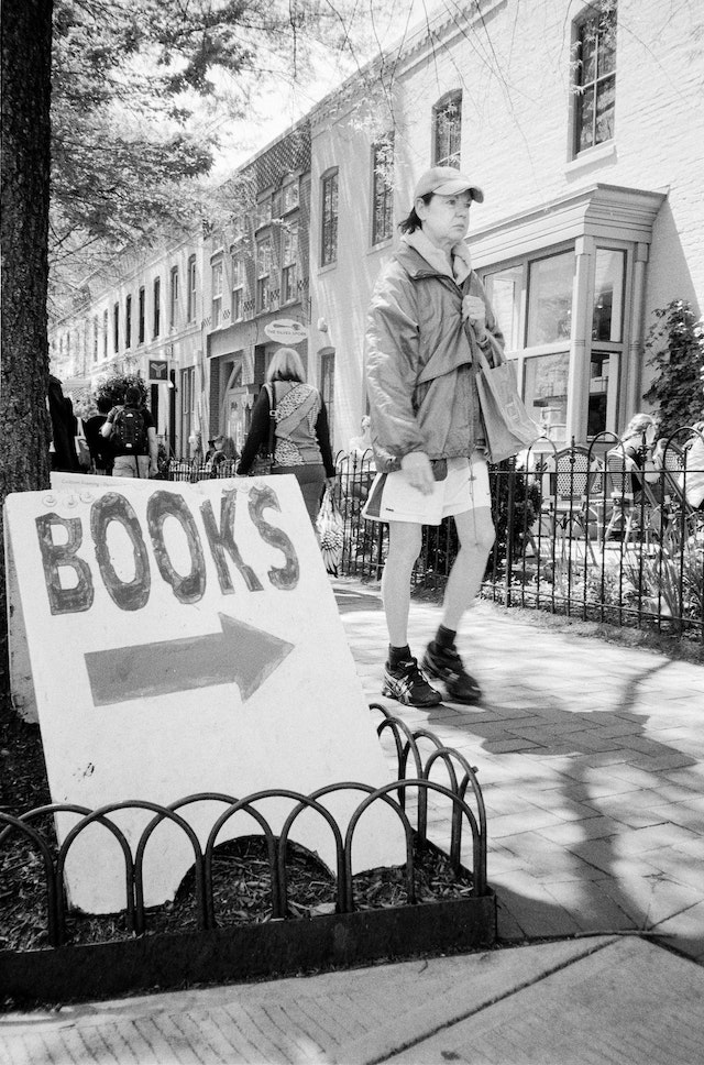 """A person walking in front of a """"books"""" sign in Eastern Market."""