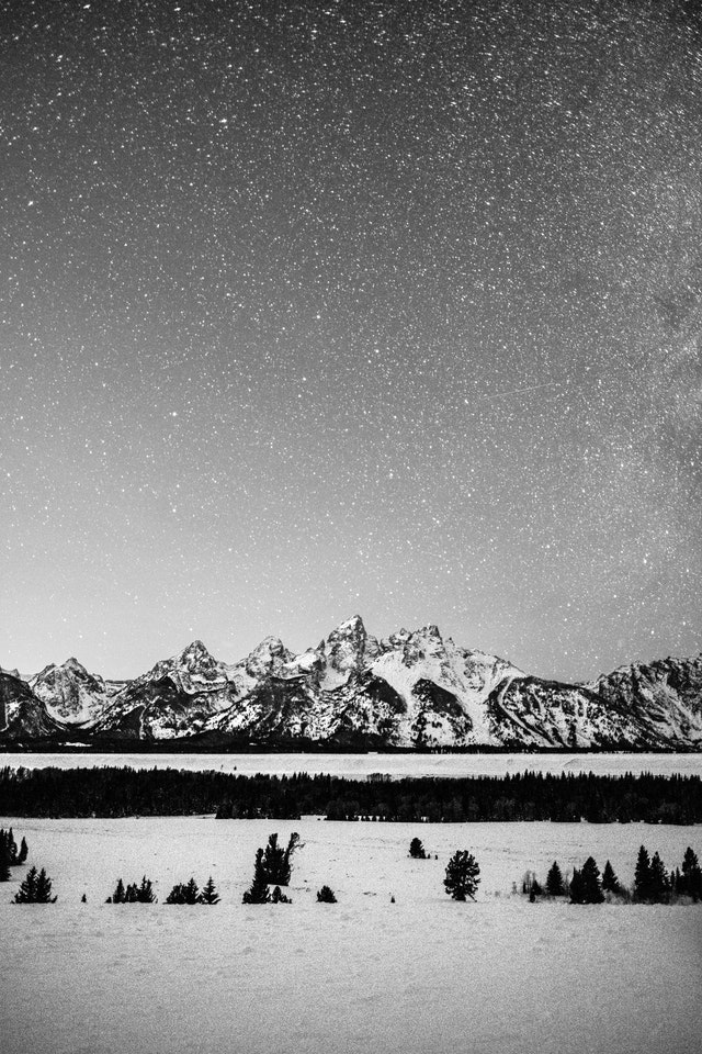 The snow-covered Teton Range seen at night under a starry sky, from the Teton Point Turnout.