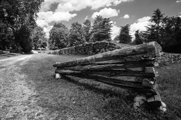 A worm fence in front of the stone wall of the sunken road at Fredericksburg National Battlefield in Virginia.