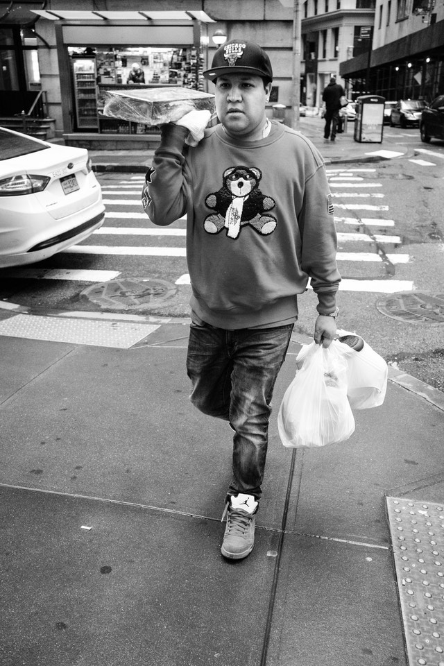 A man in a bear sweater and Chicago Bulls hat carrying food on William Street in New York.