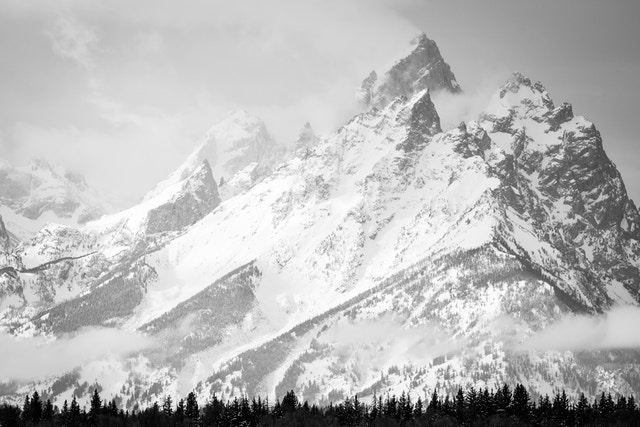 Close-up of Grand Teton and neighboring peaks, with a line of pine trees at the bottom, from the Elk Ranch Flats turnout.