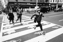 A teenager running through a crosswalk in Chinatown, Washington, DC.