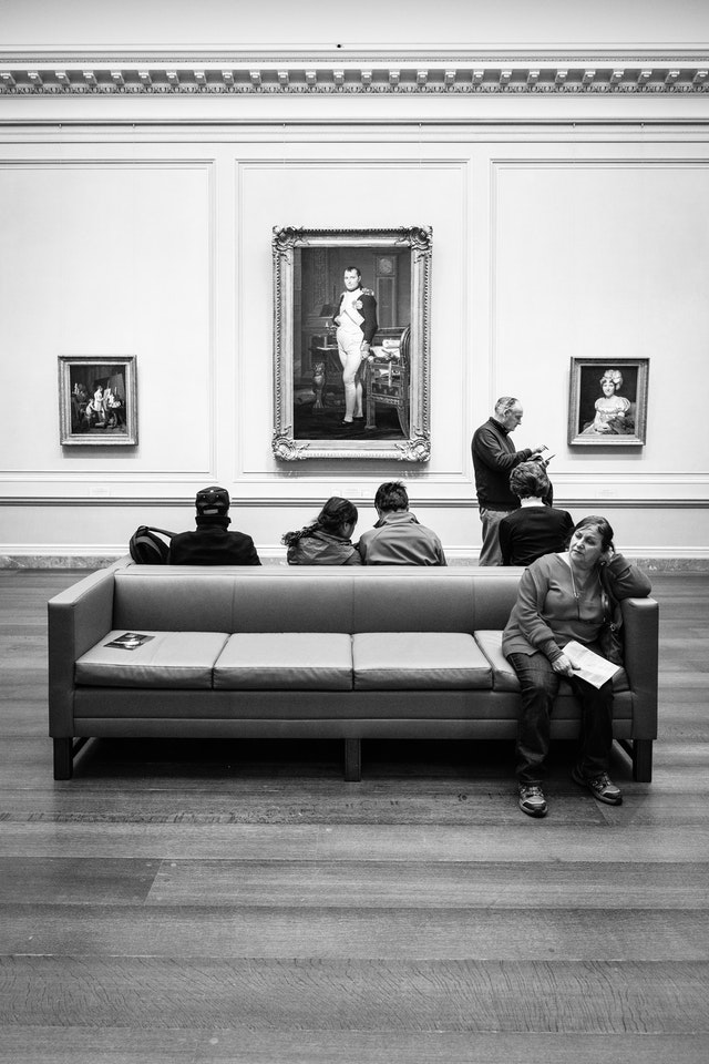 People sitting on a couch in front of a portrait of Napoleon at the National Gallery of Art.
