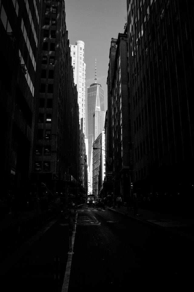 One World Trade Center, framed by buildings along John Street in the Financial District of New York.