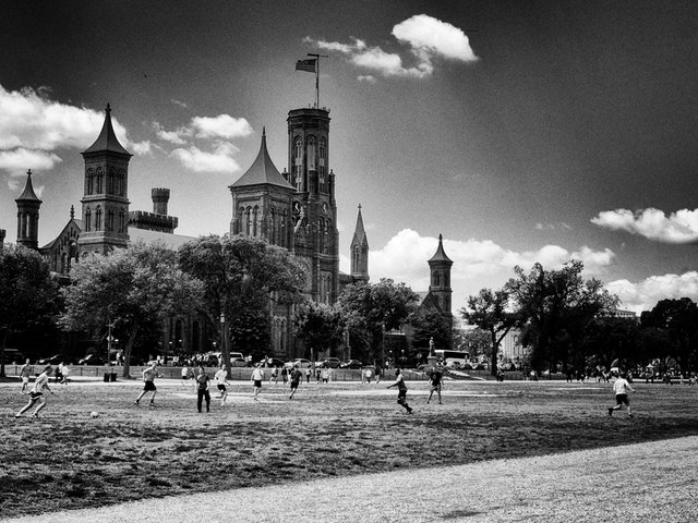 Football game on the National Mall, with the Smithsonian Castle in the background.