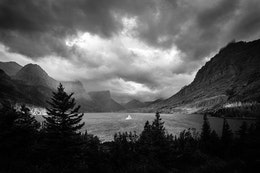 Wild Goose Island and Saint Mary Lake seen after sunrise on a very stormy morning. Wild Goose Island is the only thing lit by the sun as storm clouds swirl above.