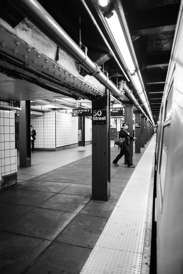 A person running to get on a train at the 50th Street station.